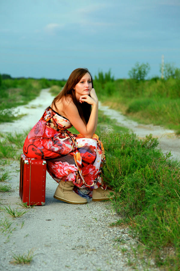 Runaway girl on suitcase. A sad, lonely runaway girl, sitting on a suitcase on a dirt road royalty free stock images