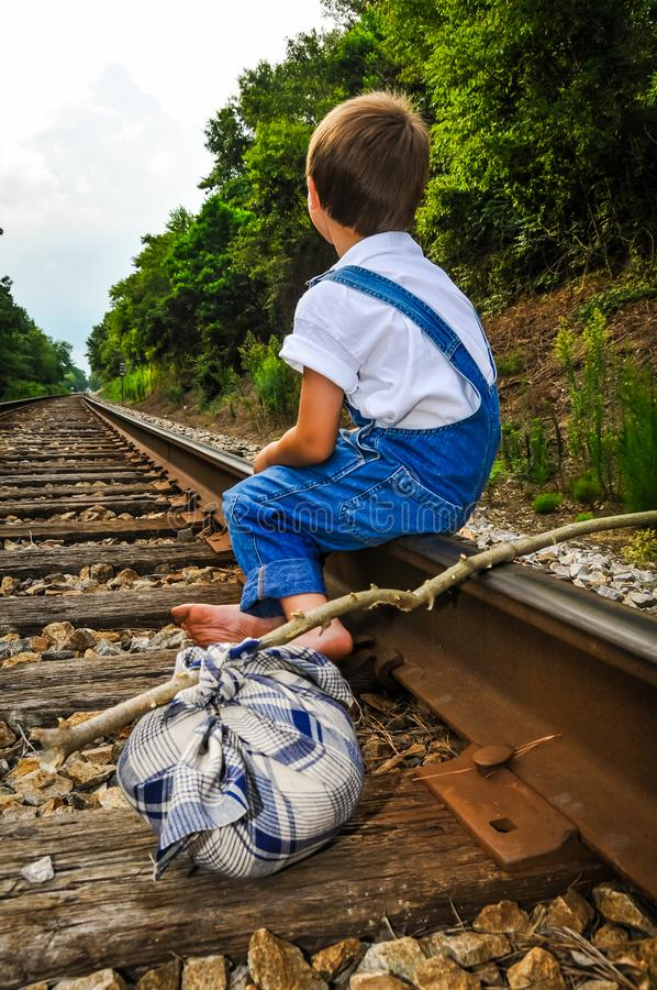 Runaway Looking for a Train. A runaway boy sitting on a train track royalty free stock images