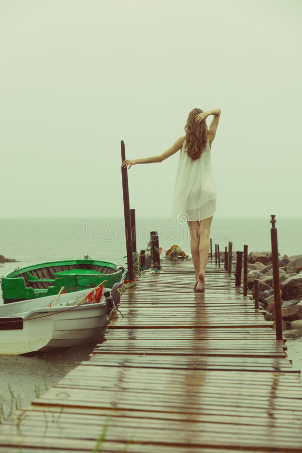 Runaway into nowhere. Girl at pier is looking for a place to escape during rainy day royalty free stock image