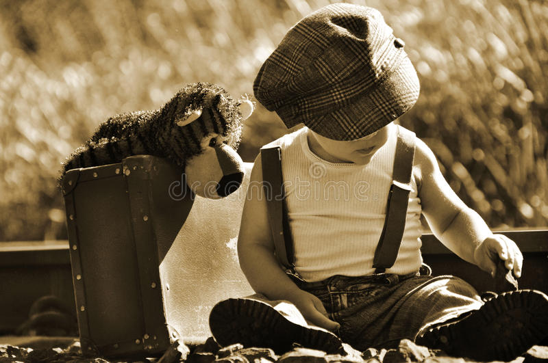 Runaway vintage sepia boy & small suitcase & teddy stock photos