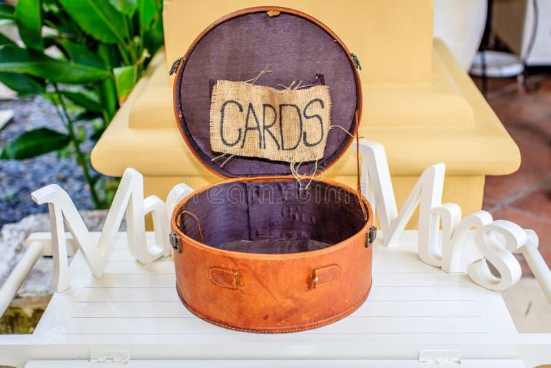 Rund brun läderask för kort, den vita träordherr och fru på sidorna Bröllopstöttor royaltyfria foton