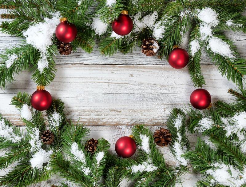 Rund gräns av röda prydnader för snöig jul som hänger på gran royaltyfri fotografi