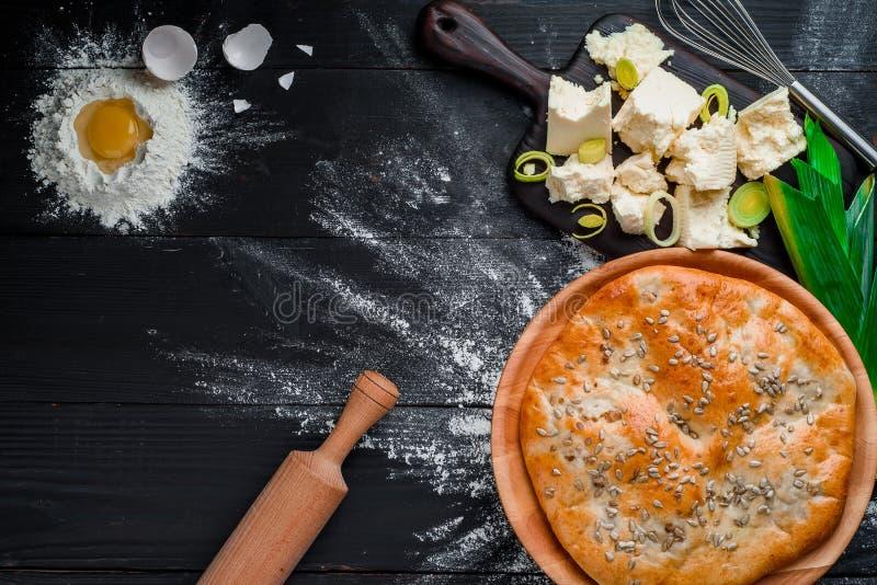 Rund hemlagad ostpaj på en svart träbakgrund i en härlig sammansättning Top besk?dar avst?nd N?rbild fotografering för bildbyråer