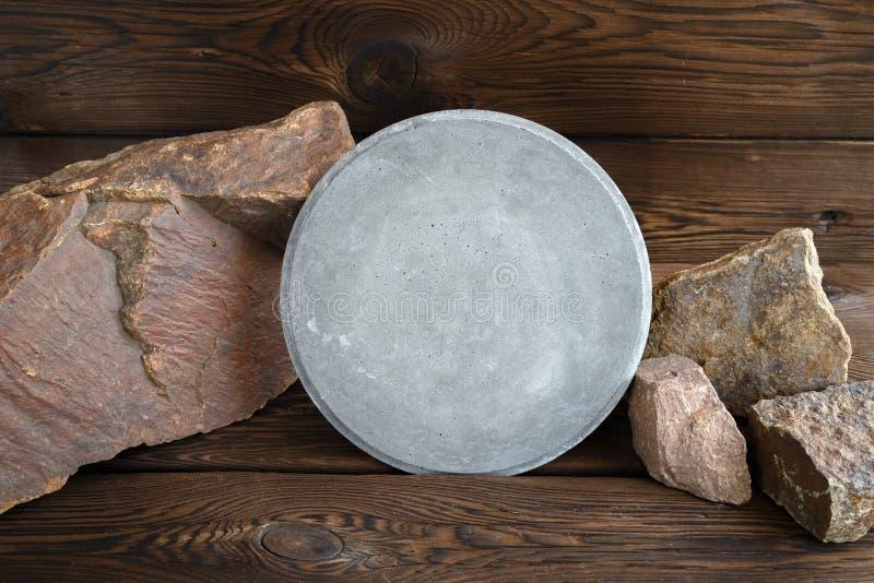 Rund konkret platta på bakgrunden av granitstenar spelrum med lampa royaltyfria foton
