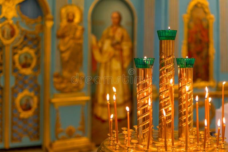 Rund ljusstake med brinnande stearinljus på bakgrunden av altaret i Christian Church arkivbilder