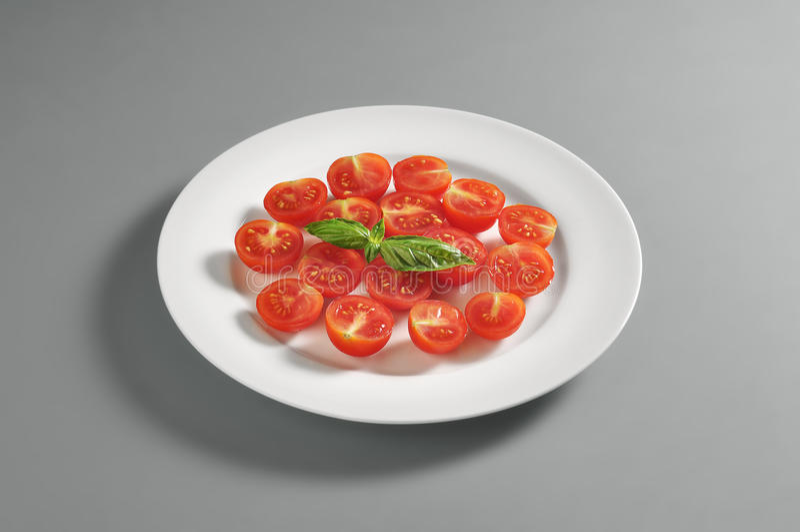 Rund maträtt med högg av körsbärsröda tomater royaltyfri fotografi