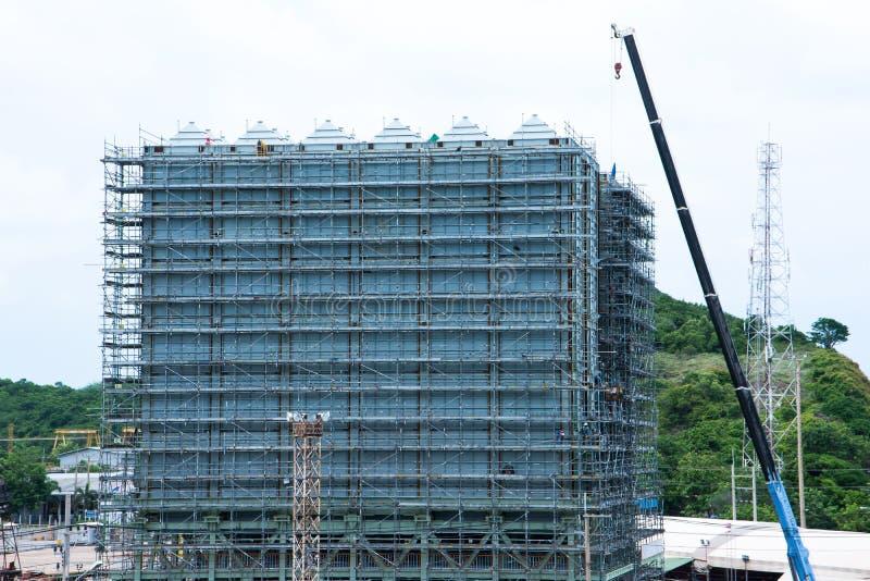 Rund nybygge för material till byggnadsställning med elevatorkranen med berget bakom royaltyfri fotografi