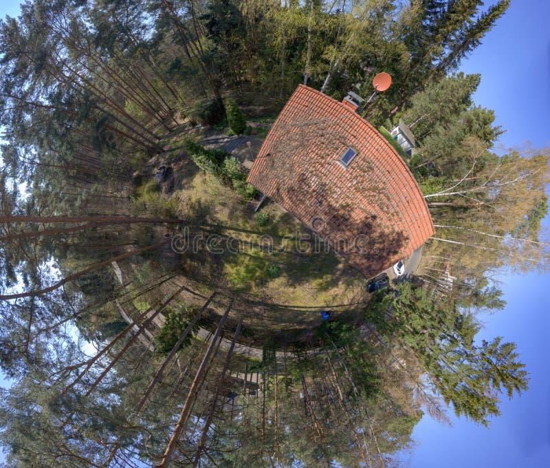 Rund panorama från sammansatta flygbilder av en liten typisk tysk småhus på en skogtäppa, avsiktligt förvridna arkivfoto