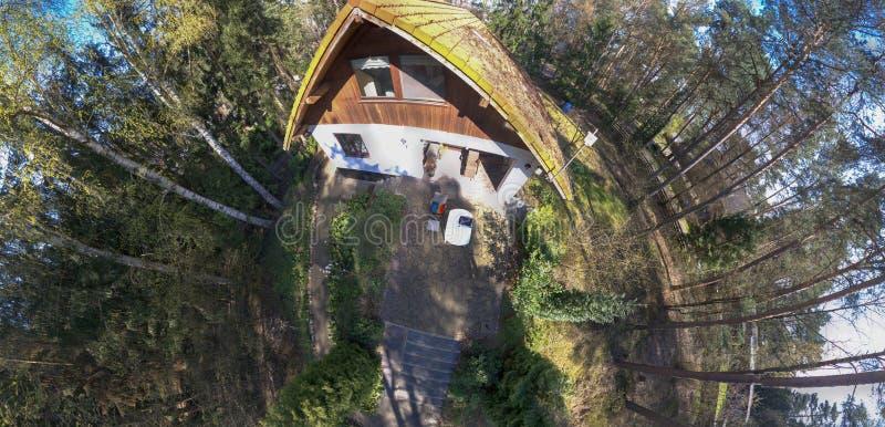 Rund panorama fr?n sammansatta flygbilder av en liten typisk tysk sm?hus p? en skogt?ppa, avsiktligt f?rvridna arkivbild