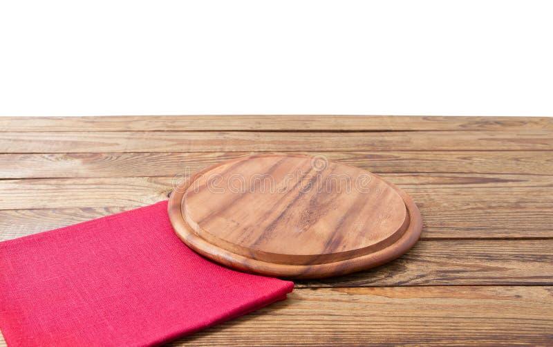 Rund pizzamatsk?rbr?da och r?d servett f?r bordduk p? den bruna tr?tabellen som isoleras p? vit bakgrund Tr?magasinplatta royaltyfria foton