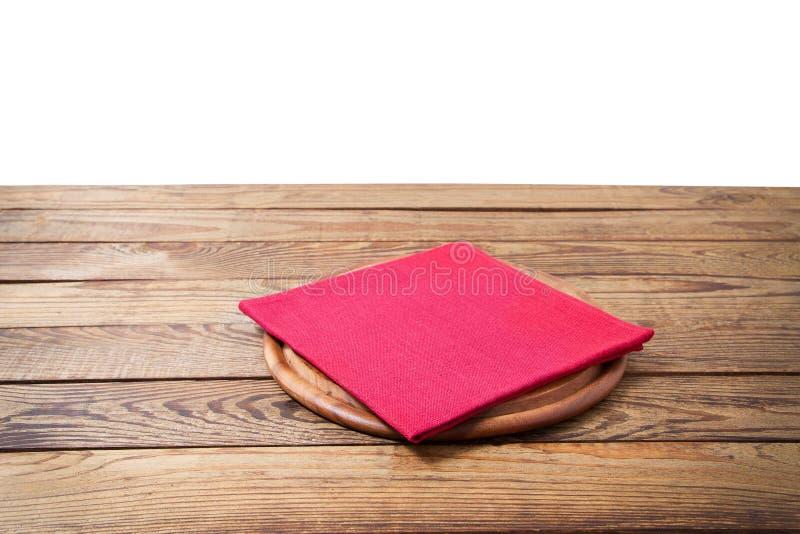 Rund pizzamatskärbräda och röd servett för tabelltorkduk på den bruna trätabellen som isoleras på vit bakgrund Trämagasinplatta arkivfoto
