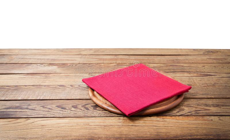 Rund pizzamatsk?rbr?da och r?d servett f?r tabelltorkduk p? den bruna tr?tabellen som isoleras p? vit bakgrund Tr?magasinplatta arkivbild