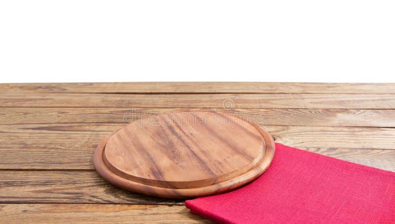 Rund pizzamatsk?rbr?da och r?d servett f?r tabelltorkduk p? den bruna tr?tabellen som isoleras p? vit bakgrund Tr?magasinplatta royaltyfri fotografi