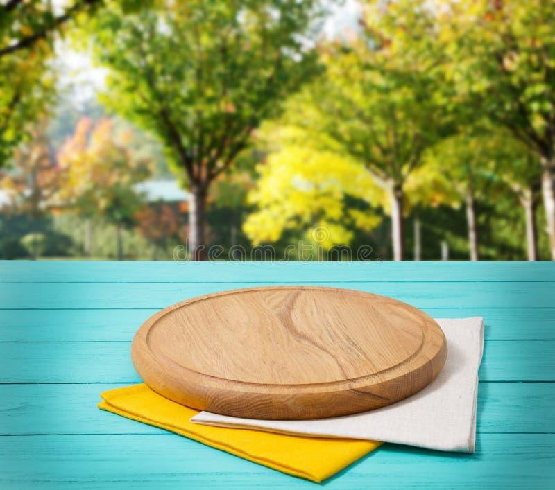 Rund pizzaskärbräda och bordduk på den blåa trätabellen med för bokehdesign för suddighet den abstrakta gröna trädgården Top besk royaltyfri fotografi