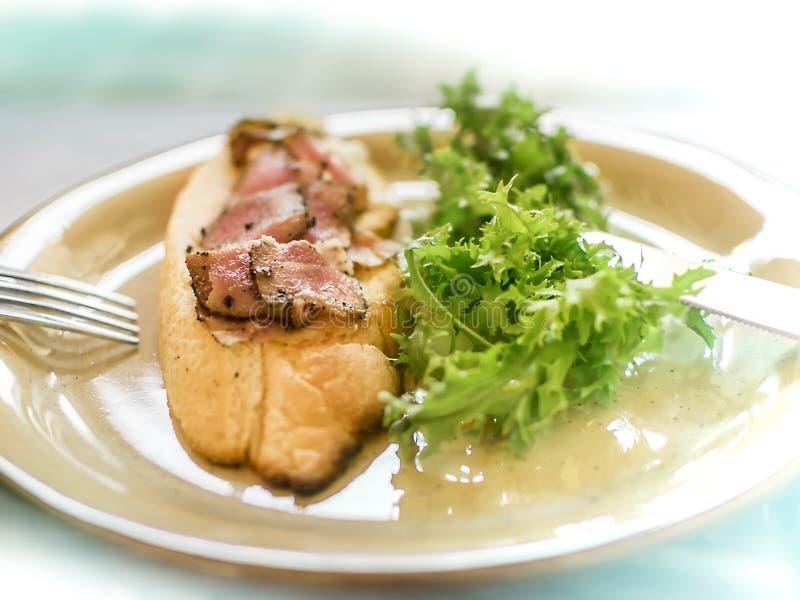 Rund platta med den aptitretande öppna smörgåsen med rostat bröd och stycken av rökt fisk och nya gröna sidor av arugula royaltyfria foton