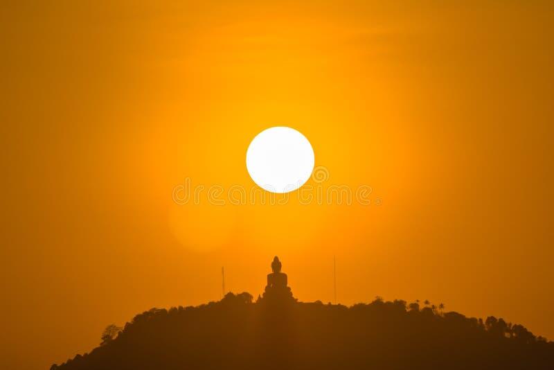 Rund röd sol ovanför stor Buddha royaltyfria bilder