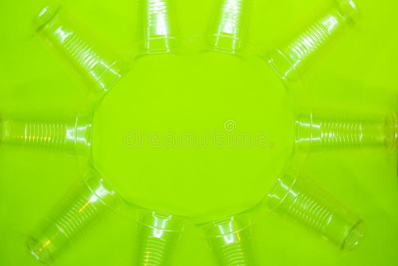 Rund ram av trasparent plast- disponibla koppar på grön bakgrund Tomt utrymme i mitten av bilden royaltyfri bild