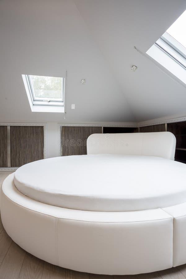 Rund rymlig säng i planlagt hus royaltyfri fotografi