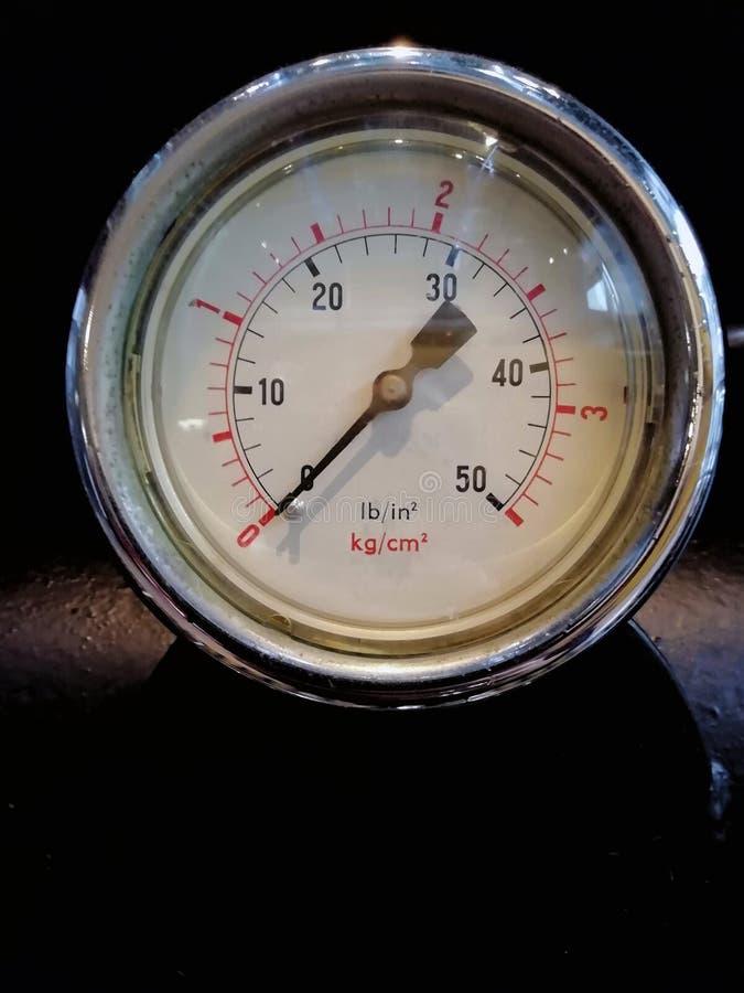 Rund skinande tryckmätare med nummer som markeras i PSI och som är meter på metervisartavlan på industriellt maskineri royaltyfria bilder