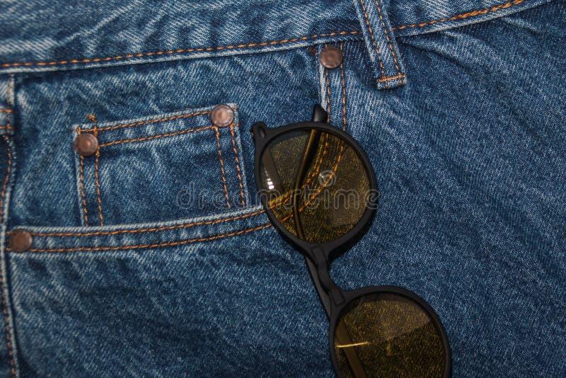Rund solglasögon på en grov bomullstvilltexturbakgrund runt gult fack för exponeringsglas framtill av jeans Grovt grov bomullstvi royaltyfria foton