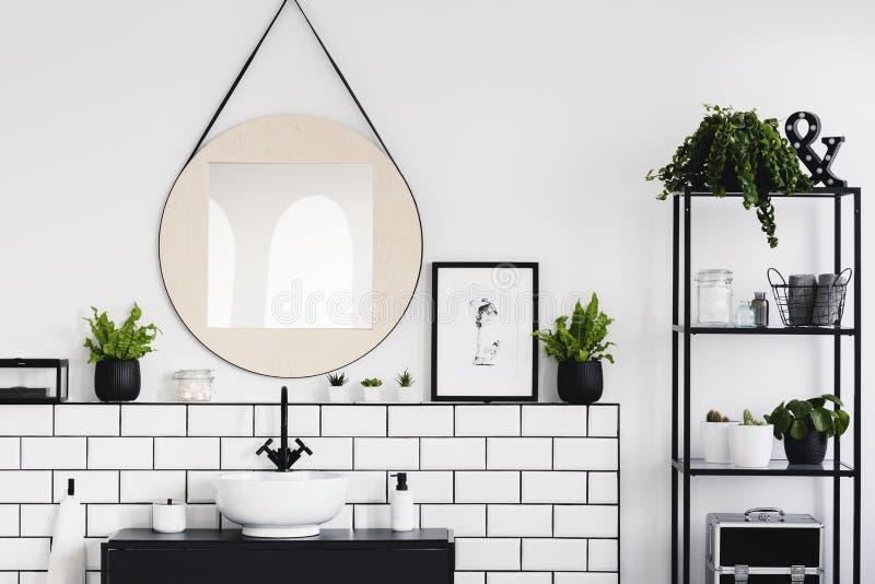 Rund spegel och affisch mellan växter i vit och svartbadruminre med handfatet Verkligt foto arkivfoto