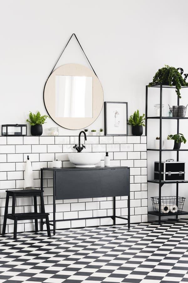 Rund spegel ovanför den svarta handfatet i modern badruminre med det rutiga golvet Verkligt foto arkivbilder