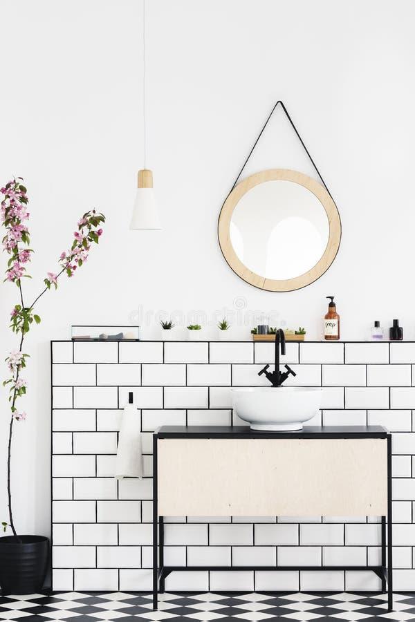 Rund spegel på den vita väggen ovanför handfatet i modern badruminre med växten Verkligt foto arkivbilder