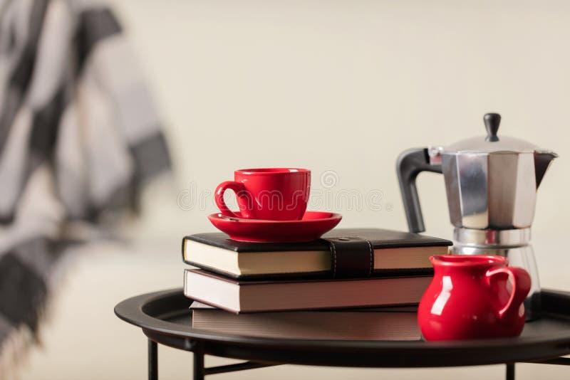 Rund svart metallkaffetabell med en kaffebryggare och en kopp med böcker på bakgrunden av en vit soffa med en grå pläd royaltyfri foto