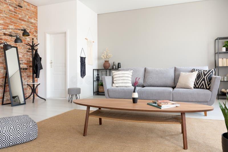 Rund trätabell i mitt av elegant vardagsrum med den gråa soffan, metallhyllan och spegeln, verkligt foto med kopieringsutrymme royaltyfria bilder