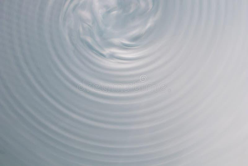 Rund vågrörelse i ett fluid system bakgrund för blåa grå färger för royaltyfri bild