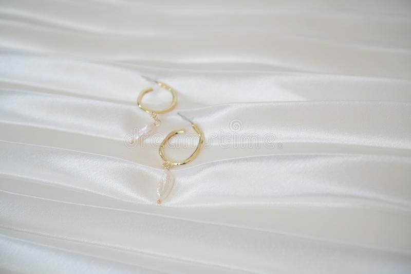 Runda guld- örhängen med pärlor ligger på en draperad vit satängbakgrund Stilfull guld- sommartillbehör för kvinnor banermall royaltyfri fotografi