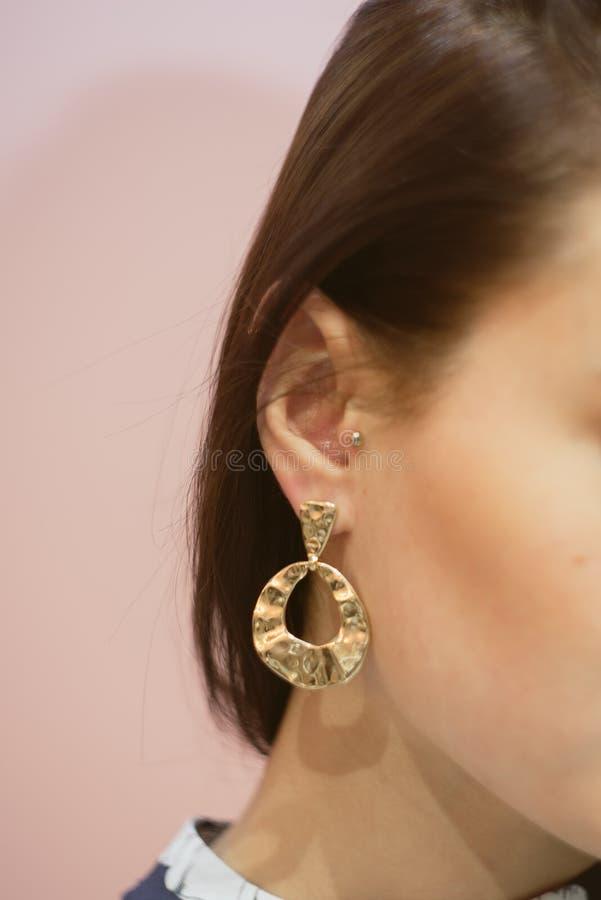 runda guld- örhängen på örat av en brunett på en rosa pastellfärgad bakgrund royaltyfri bild