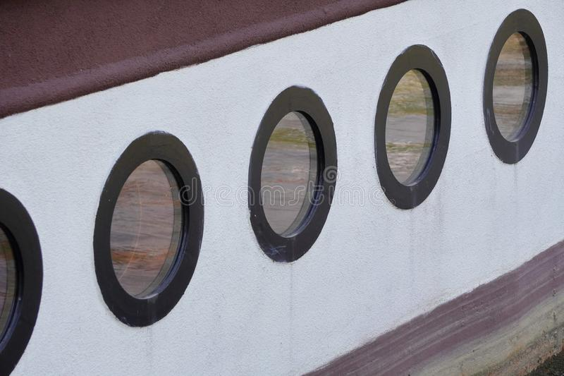 Runda hyttventiler på ett flodnöjefartyg, shipboard, vattenreflexion i fönstret, det gamla skeppet royaltyfri foto