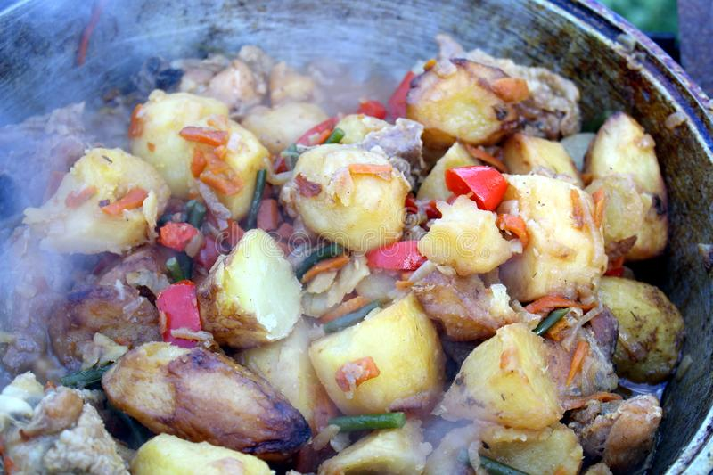Runda potatisar steker med grönsaker i en panna royaltyfria foton
