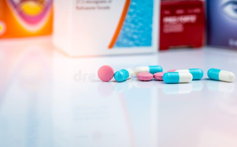 Runda rosa piller för minnestavlapiller- och vit-blått kapsel på suddig bakgrund av att förpacka för drog r Drogbruk royaltyfri bild