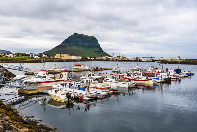 Rundarfjordur town as seen from the port. Jetty and boats are at foreground and famous Kirkjufell mountain is at background royalty free stock images
