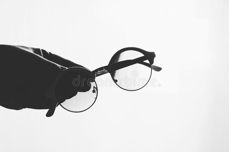 Runde Gläser in einer weiblichen Hand auf Weiß vermischten Hintergrund lizenzfreies stockbild