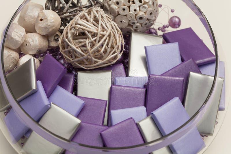 Runde Glasschüssel voll eingewickelte Schokoladen und Dekorationen stockfotografie