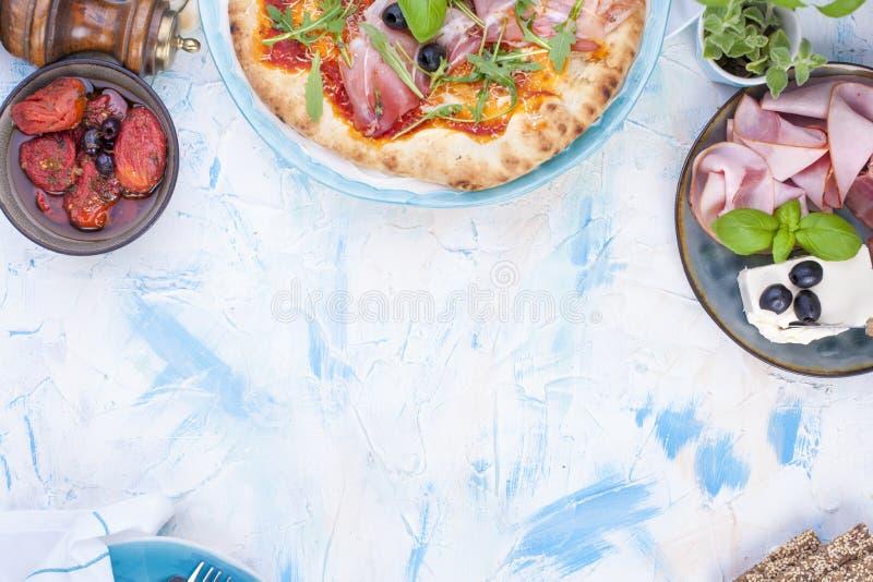 Runde große Pizza vom Ofen mit Prosciutto und Oliven, arug lizenzfreies stockfoto