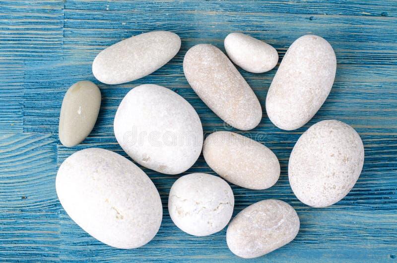 Runde helle Seesteine auf grauem blauem Hintergrund stockfoto