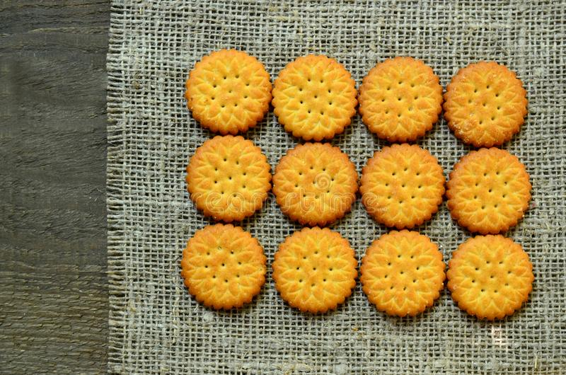 Runde köstliche salzige Crackerplätzchen auf einem Leinwandstoffhintergrund Knusperiges Backen Klassisches Snackkonzept lizenzfreies stockfoto