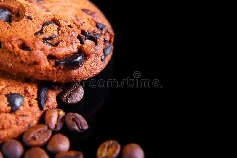 Runde knusprige Schokoladenplätzchen der Nahaufnahme mit Kaffeebohnen auf einem schwarzen Hintergrund, Makro, leerer Raum für Tex stockfotografie
