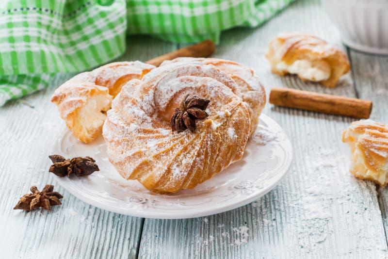Runde Kuchen mit Vanillecreme und Puderzucker auf einem Holztisch, weiße Weinlesetonware stockfoto