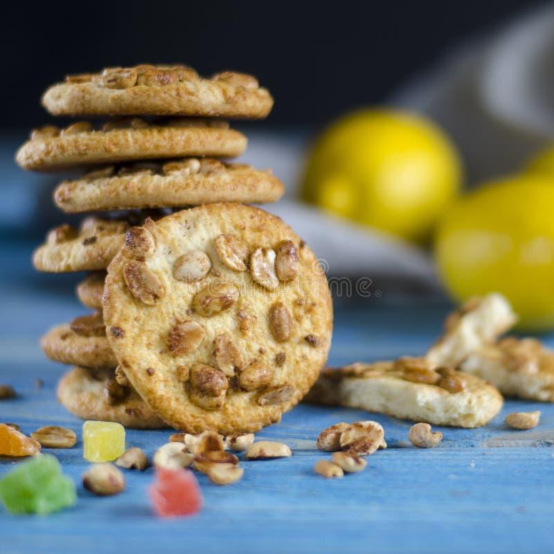 Runde orange Kekse mit bunten kandierten Fr?chten und eine Scheibe der saftigen Orange liegend auf einem Holztisch stockfotografie