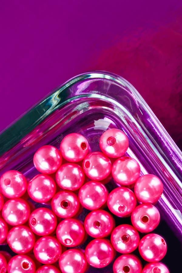 Runde rosa Perlen im Glasteller lizenzfreies stockbild