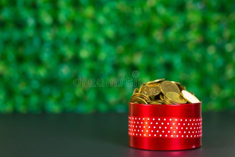 Runde rote Geschenkbox mit Bandbogen auf schwarzer Tabelle und Grünrückseite stockfotos