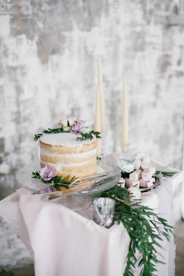 Runder Kuchen der schönen Hochzeit mit Blumendekorationen und Kerzen stockfotografie