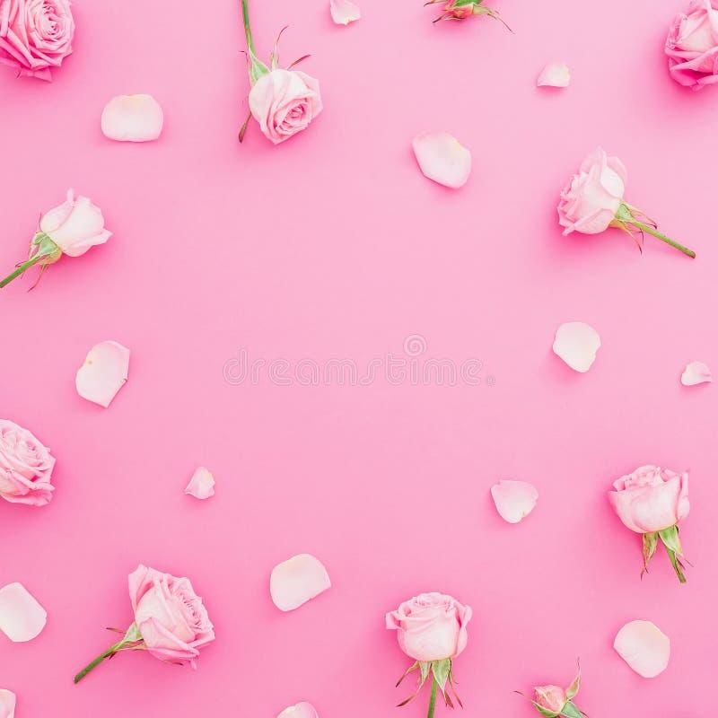 Runder mit Blumenrahmen mit Rosenblumen und -blumenblättern auf Pastellrosahintergrund Flache Lage, Draufsicht Kann als Postkarte stockfotos
