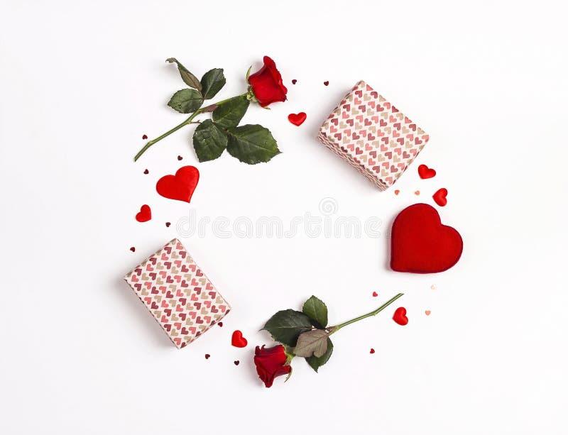Runder Rahmen gemacht von den rosafarbenen Blumen, von den Geschenken und von den dekorativen Herzen auf weißem Hintergrund Weiße stockfoto