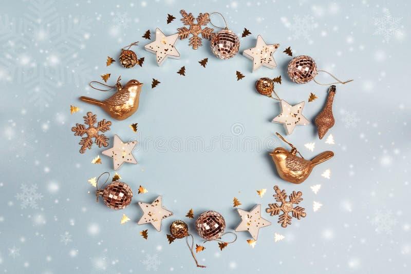 Runder Rahmen von goldenen Weihnachtsdekorationen mit Kopienraum auf blauem Hintergrund stockfoto